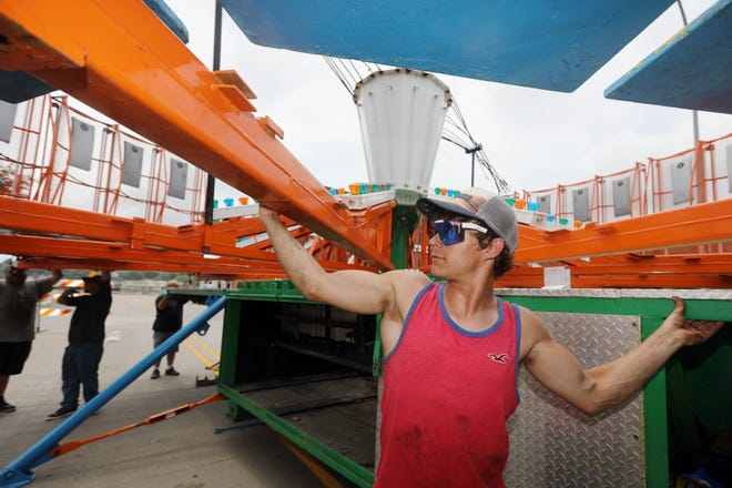 Jacob Coats with Boden Amusements helps set up the Round-Up ride Monday next to Burlington Memorial Auditorium. Workers were setting up for the carnival that starts Wednesday in conjunction with Burlington Riverfront Entertainment's Summer Concert Series that kicks off Thursday and runs through Saturday.