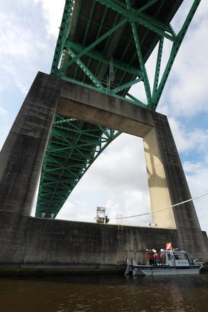 Bridge inspectors tie up under one of the supports of the Hart Bridge before putting a diver in the water to inspect one of its main concrete support piers.