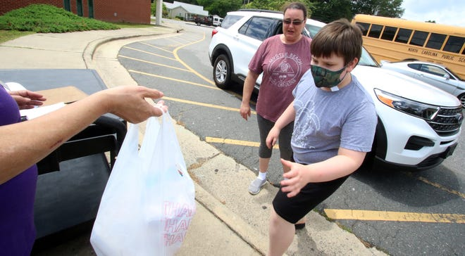 Nine-year-old Samuel Stamey picks up a free lunch as part of the Gaston County Schools' annual summer nutrition program Monday afternoon at H. H. Beam Elementary School.