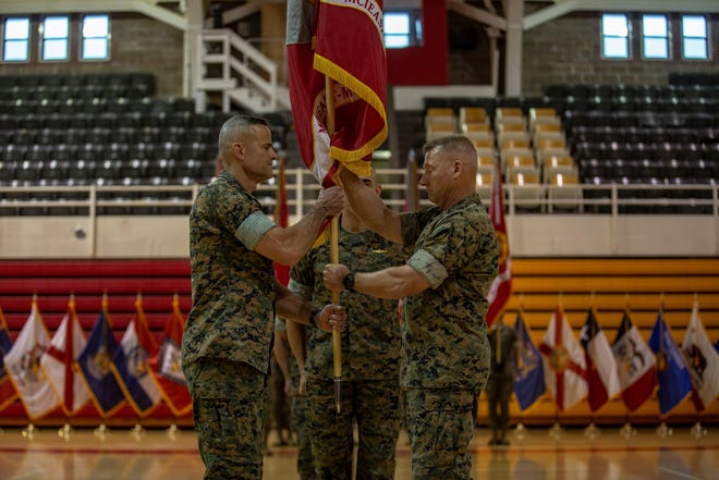 U.S. Marine Corps Maj. Gen. Julian D. Alford, right, outgoing commanding general, Marine Corps Installations East-Marine Corps Base Camp Lejeune, passes the organizational colors to Brig. Gen. Andrew M. Niebel, right, incoming commanding general for MCIEAST-MCB Camp Lejeune, during the change of command ceremony at Camp Lejeune, June 4, 2021.