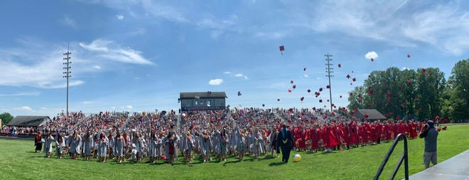 Bedford High School's Graduating Class of 2021 throws their caps up in the air in celebration during Sunday's commencement ceremony at the high school football stadium.