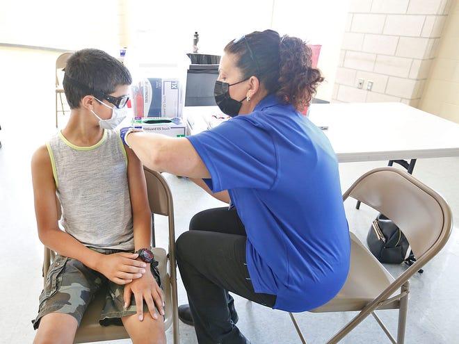 Jordan Lipner, 12, an Adams School sixth grader gets vaccinated by Brewster EMT Ann Dorsey at Weymouth High on Monday June 7, 2021.