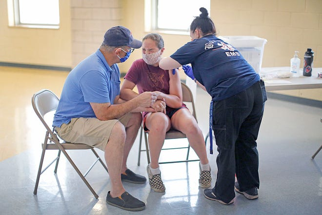 Frank DeAngelis holds daughter Isabella's hand while she gets vaccinated by registered nurse Melissa Kelleher at Weymouth High School on Monday June 7, 2021.