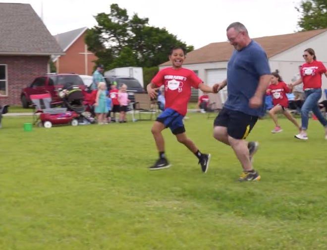Haviland third-grader Ty Hatton runs with his grandpa, Sid Colliatie, in the grandparent/grandchild race.
