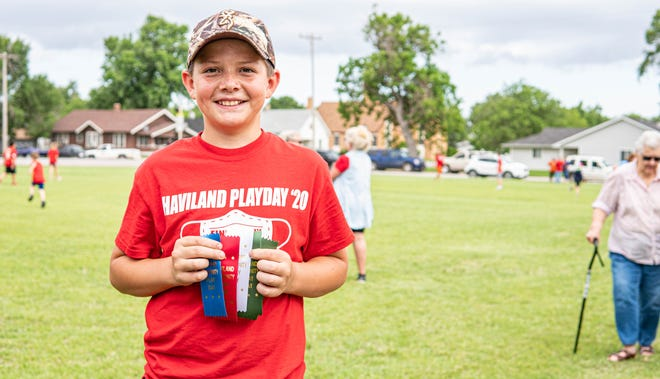 Haviland 8th Grader Tristan Sneed poses with his play day ribbons.