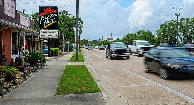 Vehicles pass free parking spaces on the side of North Ponce De Leon Boulevard in St. Augustine on Monday. The parking spaces in front of the businesses on the east side of the road are going to be removed and replaced by a bike lane.