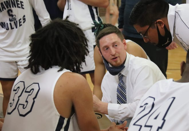 Coach Paxton Kilby (center) goes over strategy with the Shawnee High School boys' basketball team during the area tournament this past season at Tulsa Kelley. Kilby has resigned as the Wolves' coach to become an assistant at Harrah.