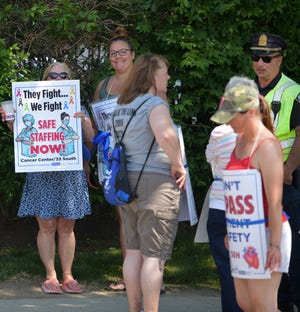 St. Vincent nurses picket on Monday, with a detail officer nearby.