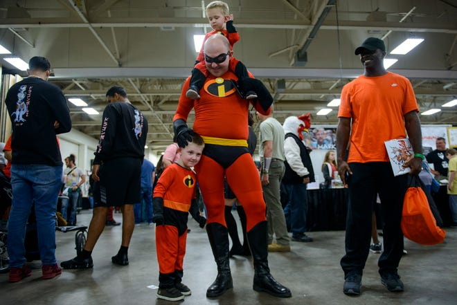 Danny Cooper, walks through the Crown Coliseum with sons Baxter, 3, by his side and Barrett, 1, on his shoulders dressed as Incredibles characters on Oct. 20, 2018 at the 2018 Comic Con.