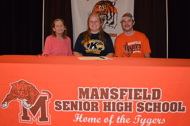 Signing a Letter of Intent is Briana Perry(center) sitting between her grandmother Pamela Crain(left) and Mansfield Senior Head Softball Coach George Goad.