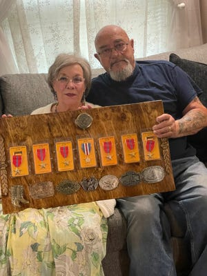 Tom and Jeanne Bayer hold a board they made for her stepfather, John Sporri, showing his military awards and part of his belt buckle collection.