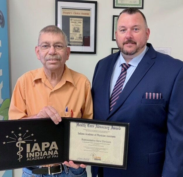State Rep. Steve Davisson, left, receives the 2021 IAPA Health Care Advocacy Award from Andrew Chastain, right, president of the Indiana Academy of Physician Assistants Board of Directors on Monday, May 24, at Good Living Pharmacy in Salem. Davisson was honored for his longtime advocacy for health care in rural areas and for supporting legislative efforts that foster a best practice environment for physician assistants across the state.