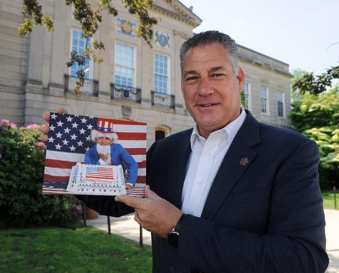 In front of Waltham City Hall, Middlesex County Sheriff Peter J. Koutoujian holds a 1980s photo of his dad, longtime Waltham City Clerk Peter Koutoujian, dressed as Uncle Sam, which was one of the first color photos to be published in the News-Tribune.