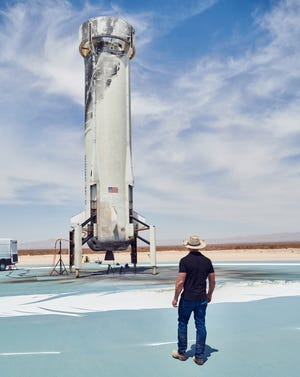 Amazon and Blue Origin founder Jeff Bezos looks up at a New Shepard booster after a successful launch and landing in Texas on April 14, 2021.