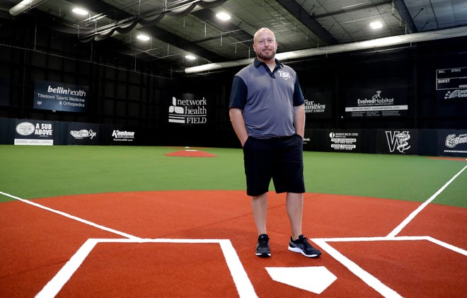 Jason Berken, former professional baseball player and West De Pere graduate, stands on the full-size infield of his newly opened Impact Sports Academy for softball and baseball players.