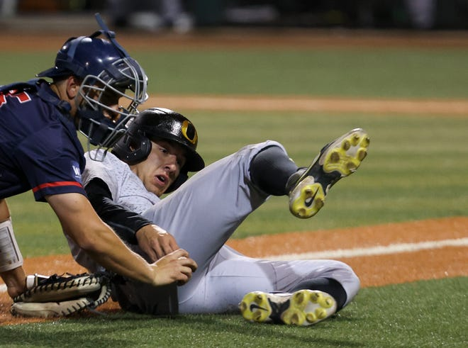 Gonzaga catcher Tyler Rando (25) chases down and tags out Oregon's Sam Novitske (9) during an NCAA college baseball regional tournament game in Eugene, Ore., Saturday, June 5, 2021. (Brian Hayes/Statesman-Journal via AP)