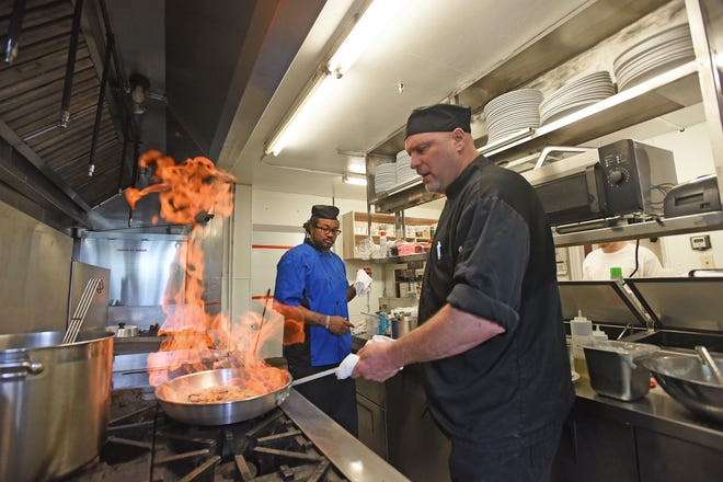 Daniel Bailey and Torence Anderson are hard at work Monday preparing for Tuesday's reopening of The Malabar Farm Restaurant.