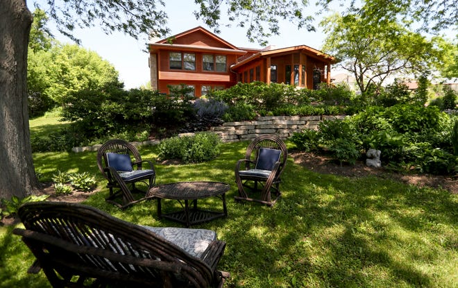 A cozy seating area sits in the backyard of Cyndy Allen's home, with a stone wall and gardens in the background,