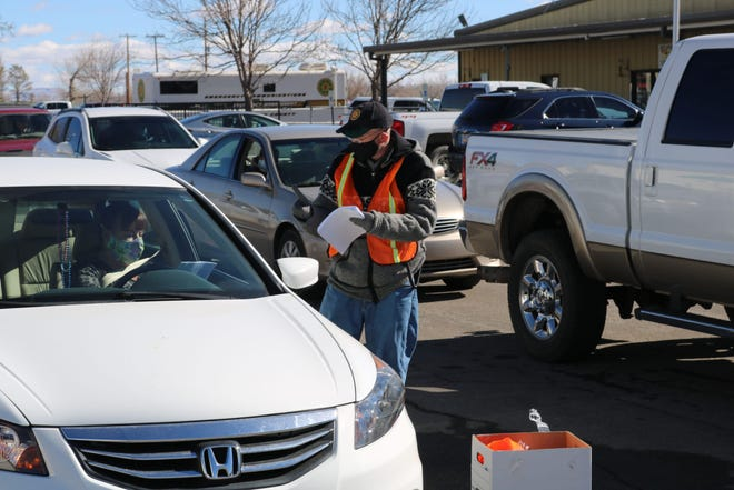 Drivers check in with a volunteer before receiving a COVID-19 vaccination on Jan. 30, 2021, during a drive-thru clinic at McGee Park outside Farmington.