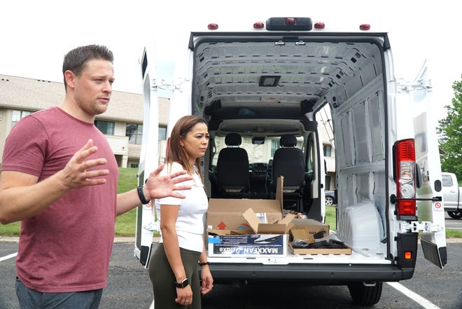Farmington Hill resident Nick Kokenos, left, talks about working on customizing a Dodge Ram Promaster van along with his girlfriend Erica Battle, right - so they can live within it as they travel the country. The couple plan on completing most of the work themselves to turn the van into a place where they can sleep, work, shower and cook as they travel around.