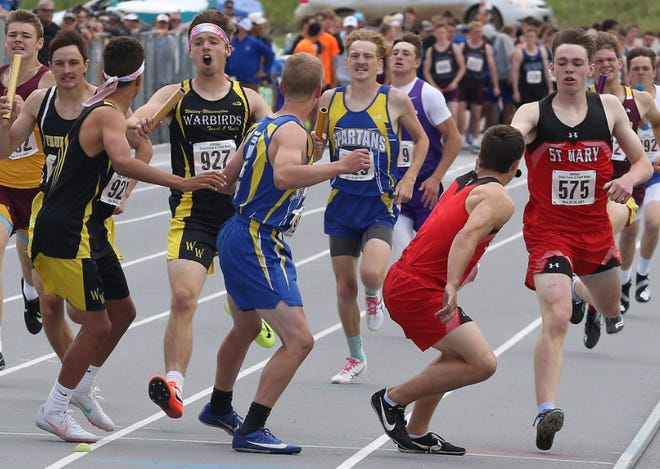 St. Mary's Nic Gaspar (right) hands off to Connor Libis in the 1600 Sprint Medley relay at the Class B State Track and Field meet in Rapid City on May 29, 2021.