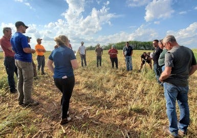 Nick Guilette, holding shovel, answers questions about no-till planting and its benefits at a Peninsula Pride Farms Conservation Conversation  at Aaron Augustian's farm in Carlton, Wis.