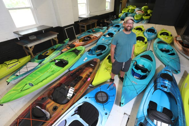 Bear Davis stand amid some of the kayaks that will soon be plying the waters of the Muskingum and Licking rivers from Pea Ohana Water Sports on Muskingum Avenue in Zanesville.