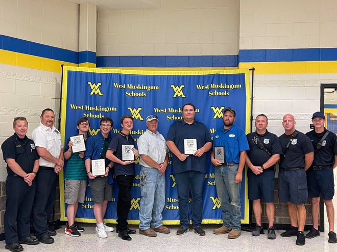 The Falls Township Fire Department awarded four students and one employee at West Muskingum for helping a man trapped underneath a lawnmower. Pictured between firefighters from left to right are civilians  Slade Bee, Connor Allison, Andrew Haag, Chris McPherson, Zach Strunk, and Cody Kelley.