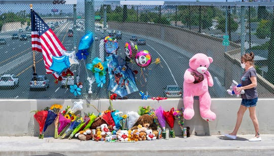 Susan Kellogg brings two stuffed toy animals to a growing memorial on an overpass of the 55 freeway in Orange, California. 6-year-old Aiden Leos was shot and killed during a road-rage attack in late May, authorities say.