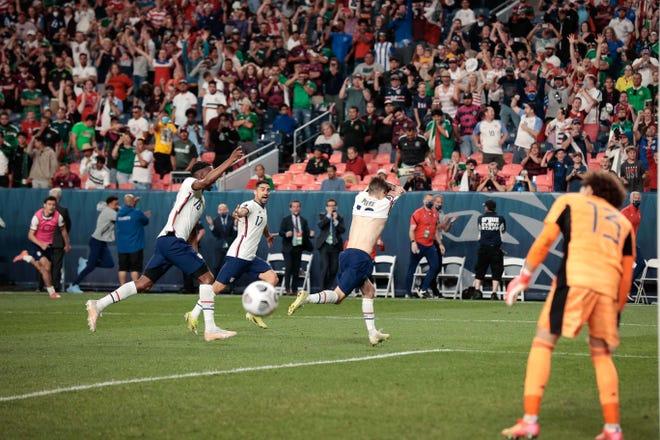 Christian Pulisic celebrates after scoring on a penalty kick.