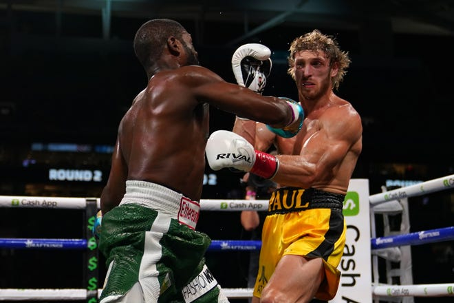 Floyd Mayweather Jr. (left) fights Logan Paul (right) during an exhibition boxing match.