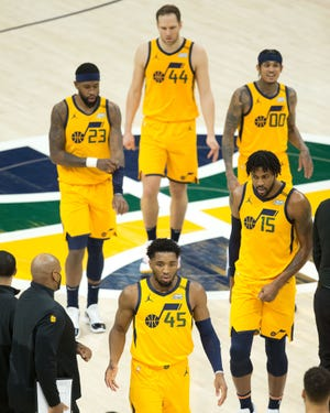 Jazz guard Donovan Mitchell (45) and center Derrick Favors (15) and guard Jordan Clarkson (00) and forwards Bojan Bogdanovic (44) and Royce O'Neale (23) walk off the court during a time out in the first half against the Memphis Grizzlies at Vivint Smart Home Arena.