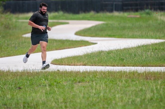 Weston Everett takes his afternoon jogs in the Blackhawk neighborhood in Pflugerville on Tuesday. Rain has increased the grass and mold allergens in the region lately.