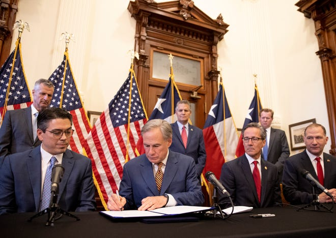 Gov. Greg Abbott signs legislation into law at the Capitol on Tuesday to reform the Electric Reliability Council of Texas. Watching him are, seated left to right, state Rep. Chris Paddie, R-Marshall, state Sen. Kelly Hancock, R-North Richland Hills, and state Sen. Charles Schwertner, R-Georgetown. Standing, left to right, are ERCOT CEO Brad Jones, Williamson County Judge Bill Gravell and Public Utilities Commission Chair Peter Lake.