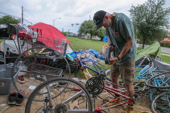 """A man who would only give """"Bones"""" as his name works on repairing a bicycle tire Tuesday at a homeless camp on East Riverside Drive."""