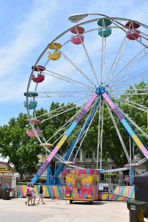 Women walk past the ferris wheel at the National Sand Bass Festival in Madill Tuesday, June 8, 2021. Food vendors at the festival open at 11 a.m. each day through Friday.