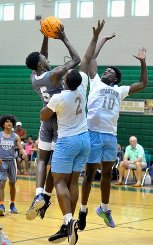 A Greenbrier player goes up for a shot against Glenn Hills defenders during a summer league basketball game on Monday, June 7, 2021 at Josey High School. [WYNSTON WILCOX/THE AUGUSTA CHRONICLE]