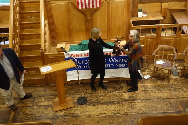 Mimi McConnell presents the Mercy Otis Warren Cape Cod Woman of the Year statuette to Wendy Northcross, CEO of the Cape Cod Chamber of Commerce, at a June 2 ceremony inside the 1717 Meetinghouse in West Barnstable.