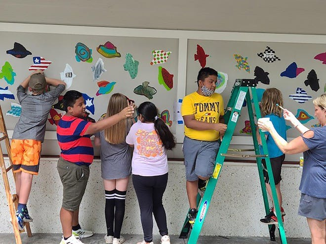 M.C. Riley Elementary art students create a mural last weekend at the Oscar Frazier Park pavilion.