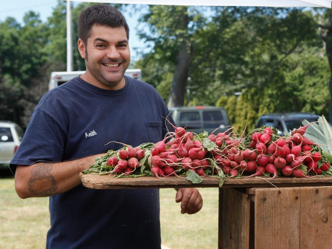 Keith Branco from Silver Brooke Farm poses next to fresh organic radishes at a past Osterville Farmers Market.