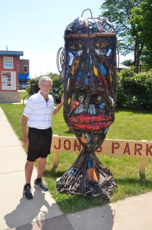 Don Heller is pictured standing next to the sculpture on the corner of Main and Chestnut in Jones Park.