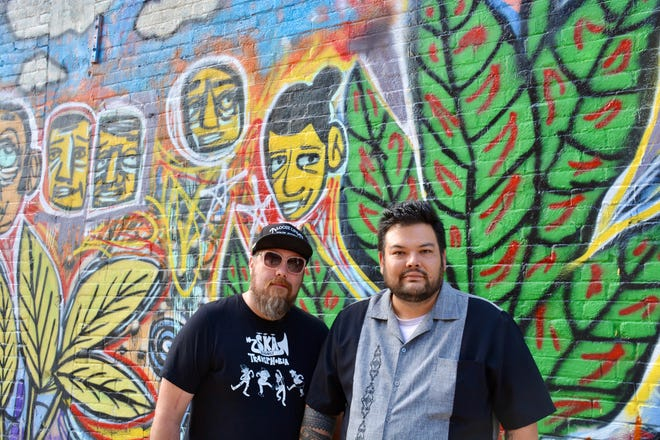 Chad Kessler, left, and Christopher Cropper in front of a mural they painted on the patio of Oddfellows Liquor Bar and Mikey's Late Night Slice in the Short North.