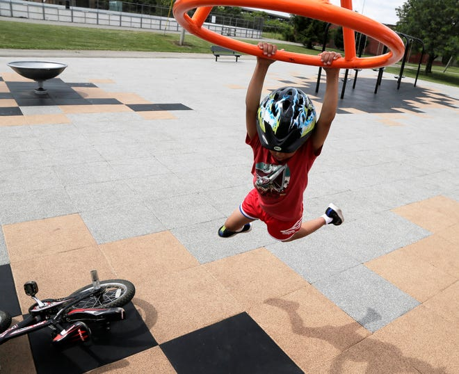 Ebenezer Files, 6, of Ganthers Place on Columbus' South Side, hangs on a ring on the playground at Dodge Recreation Center Tuesday.