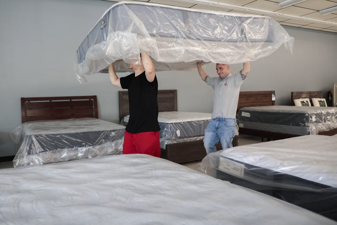 Inventory manager Travis Nolan, left, and owner Chris Robbins move a mattress at Columbus Mattress Wholesale's new location in Gahanna.