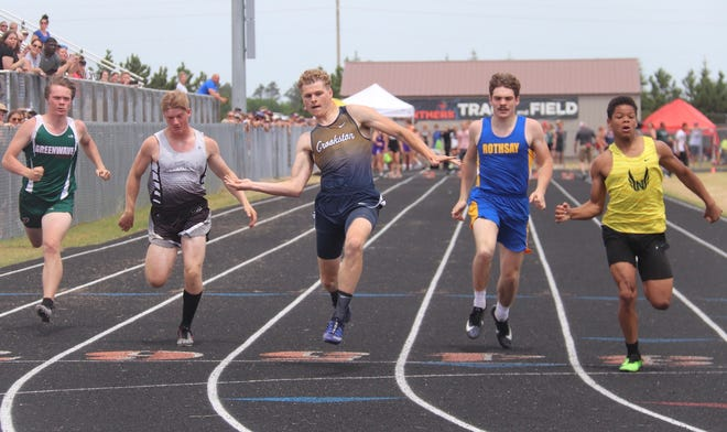 Noah Kiel celebrates as he crosses the finish line first in the 100-meter dash.