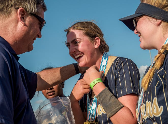 Eustis pitcher Libby Levendoski (6) smiles after receiving her gold medal from Eustis Athletic Director Harry Tomlinson after the Panthers blanked Brooksville Hernando 5-0 on May 21 in the Class 4A state championship game at Legends Way Ball Fields in Clermont. [PAUL RYAN / CORRESPONDENT]