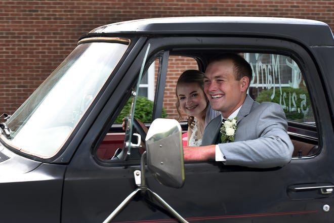 Big smiles are shown by both Tye and Holly Thompson, of Dundee as the couple drive away in their 1987 Dodge Ram pickup on May 21 after being married at the Blissfield Baptist Church.