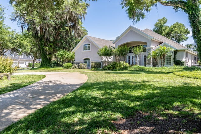 This luxury pool home sits on a corner lot in Ormond Lake's gated section of Emerald Lakes Estates.
