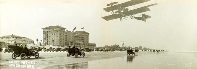 Cars and a Wright airplane parade on the beach next to the newly rebuilt Clarendon Hotel in 1911.