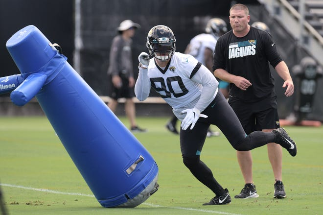 Jaguars defensive line coach Tosh Lupoi looks on as Taven Bryan runs through tackling dummies during a minicamp practice last week.
